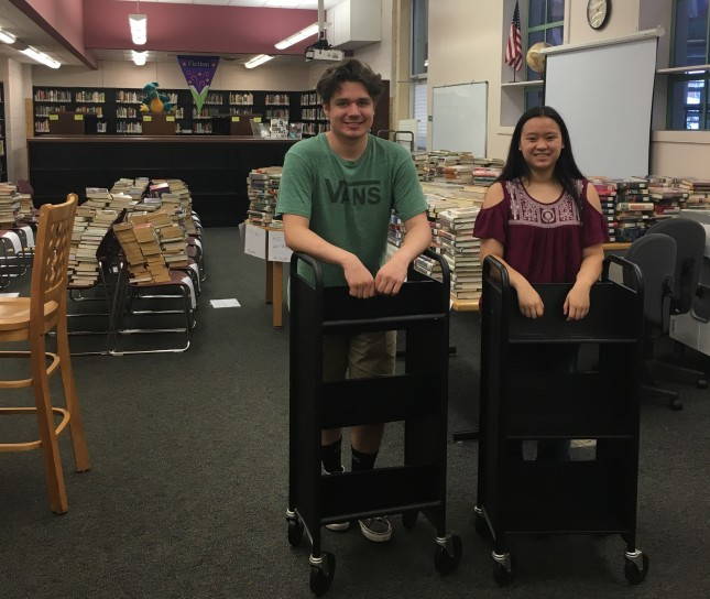 Harrison and Megan posing with empty book carts in front of stacks of books they emptied from the library's freestanding bookcases