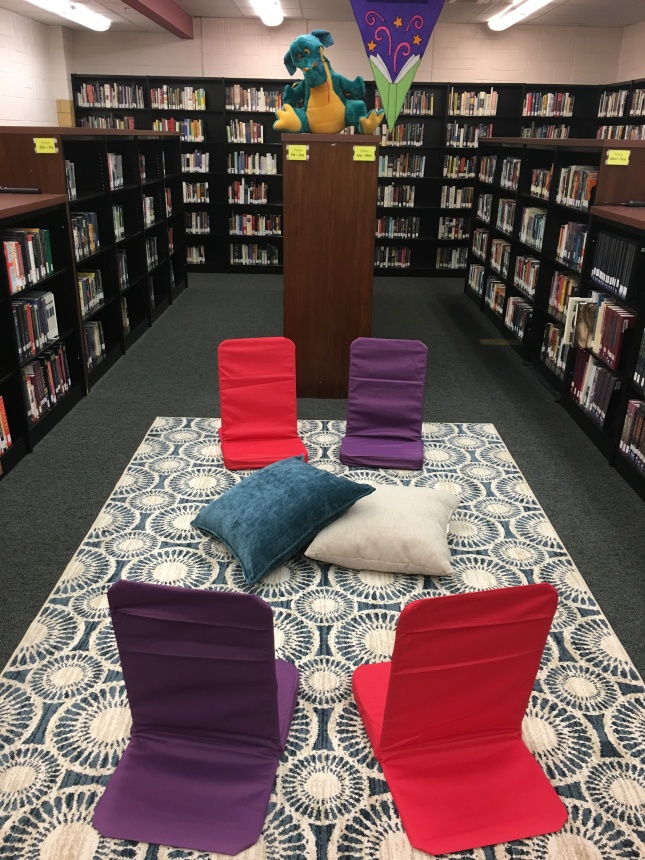 Relaxed reading area with floor chairs, a funky rug, and lap desks.