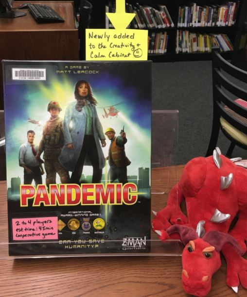 image of the Pandemic board game with a red stuffed dragon beside it