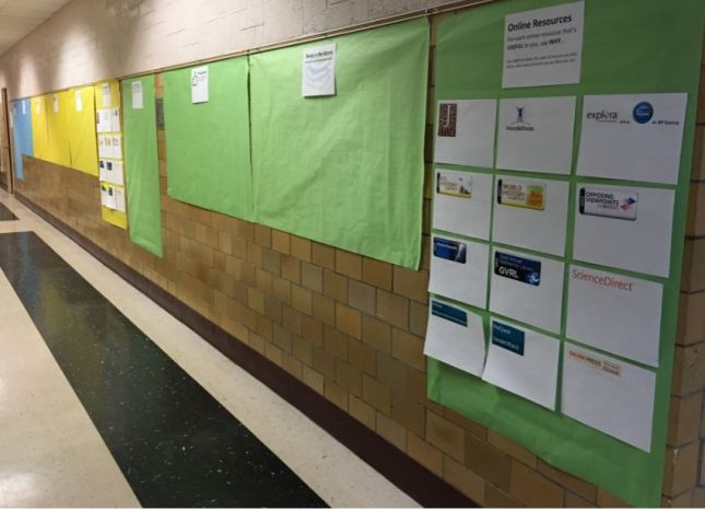 series of posters in hallway - green, gold, and blue - on which students can leave feedback about the library
